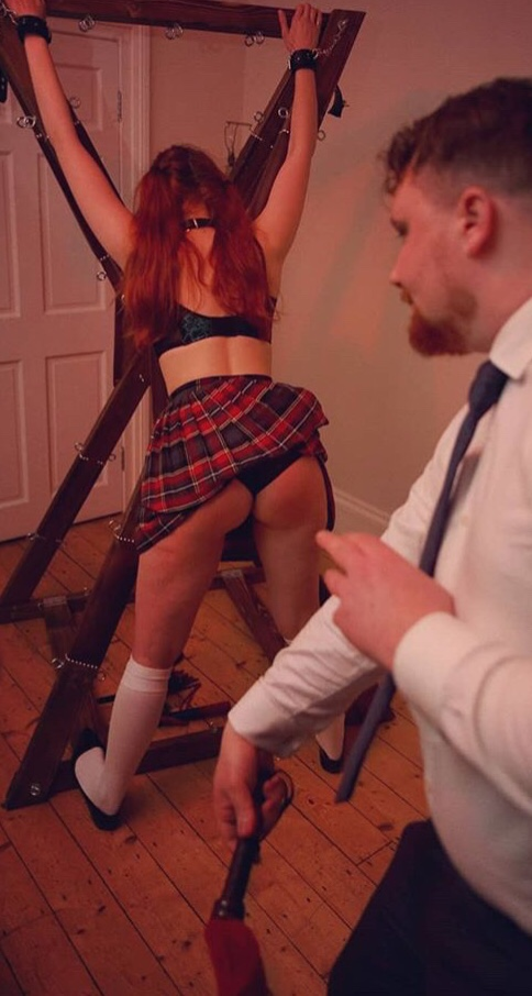 beautiful red haired woman being flogged against a cross by a dominant bearded man