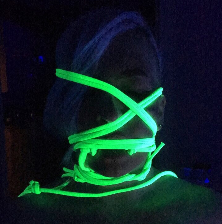 Woman's face wrapped in glowing rope