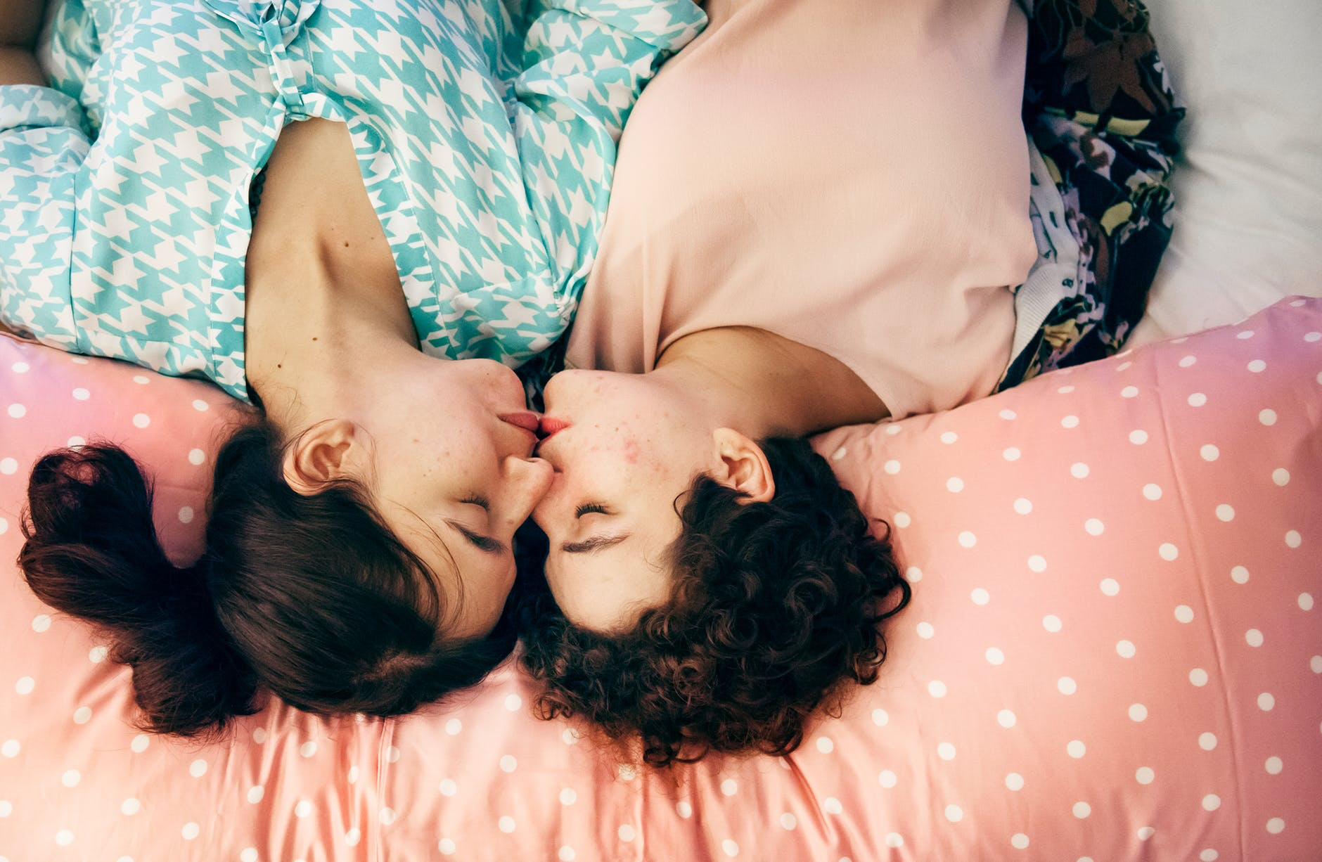 Two people kiss lying down
