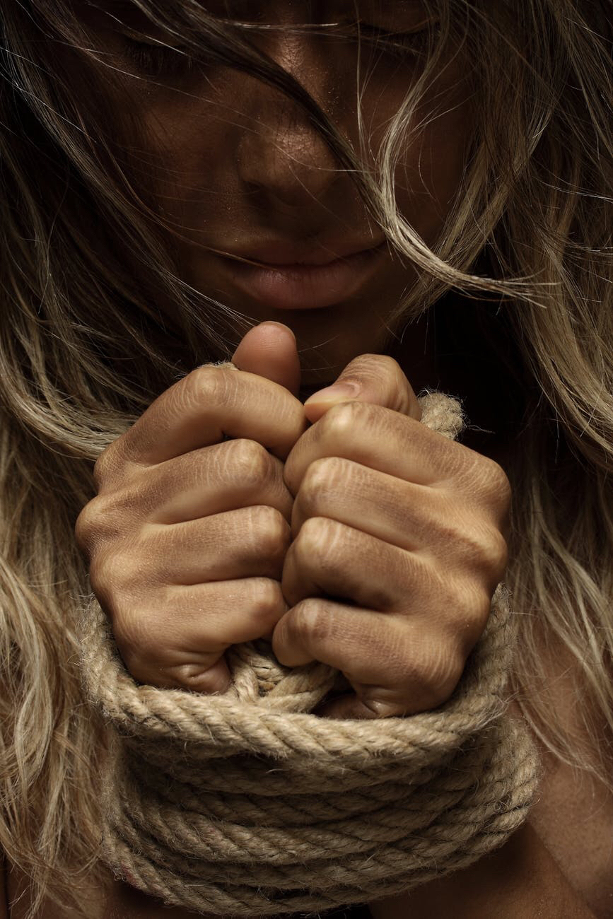 Blonde woman with hands bound in rope