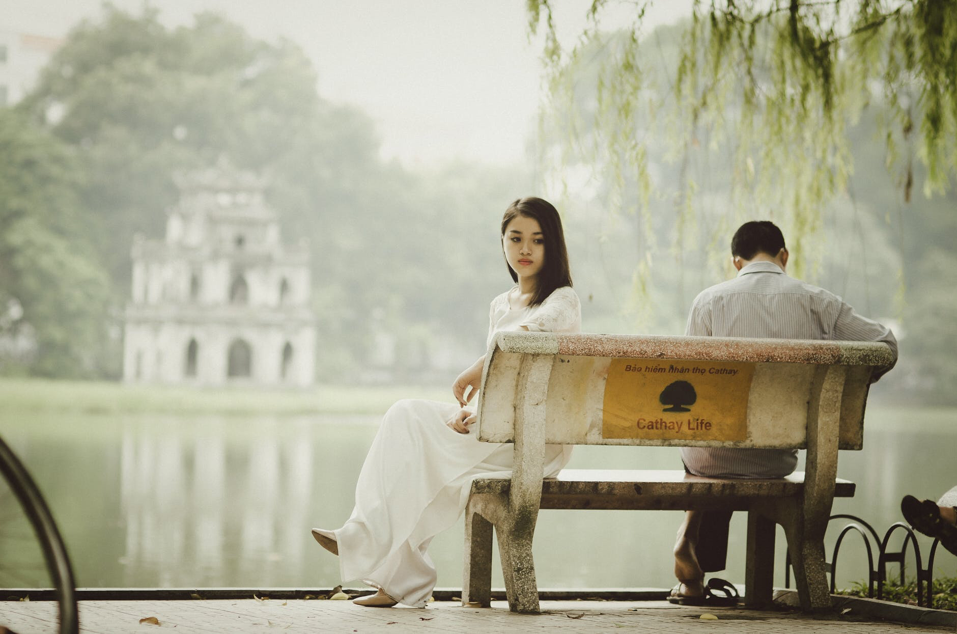Couple sits sadly apart on a bench by a lake