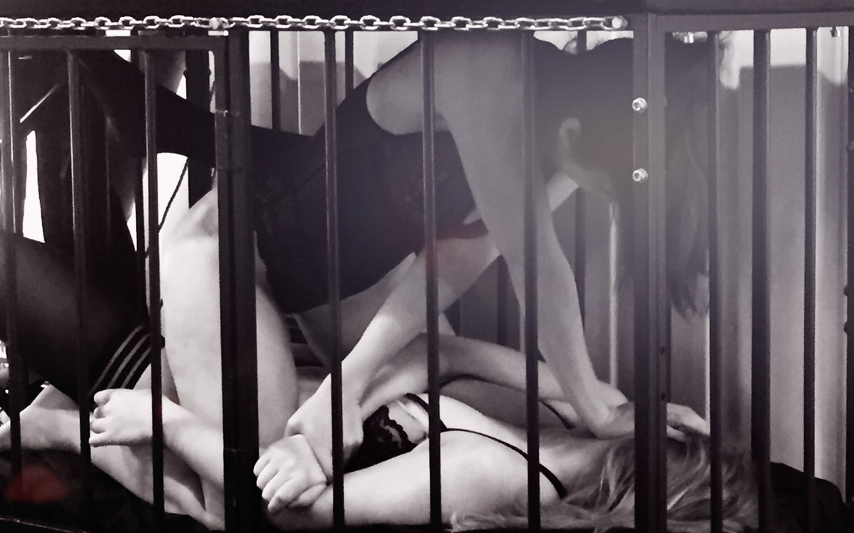 Two women wrestle in a cage