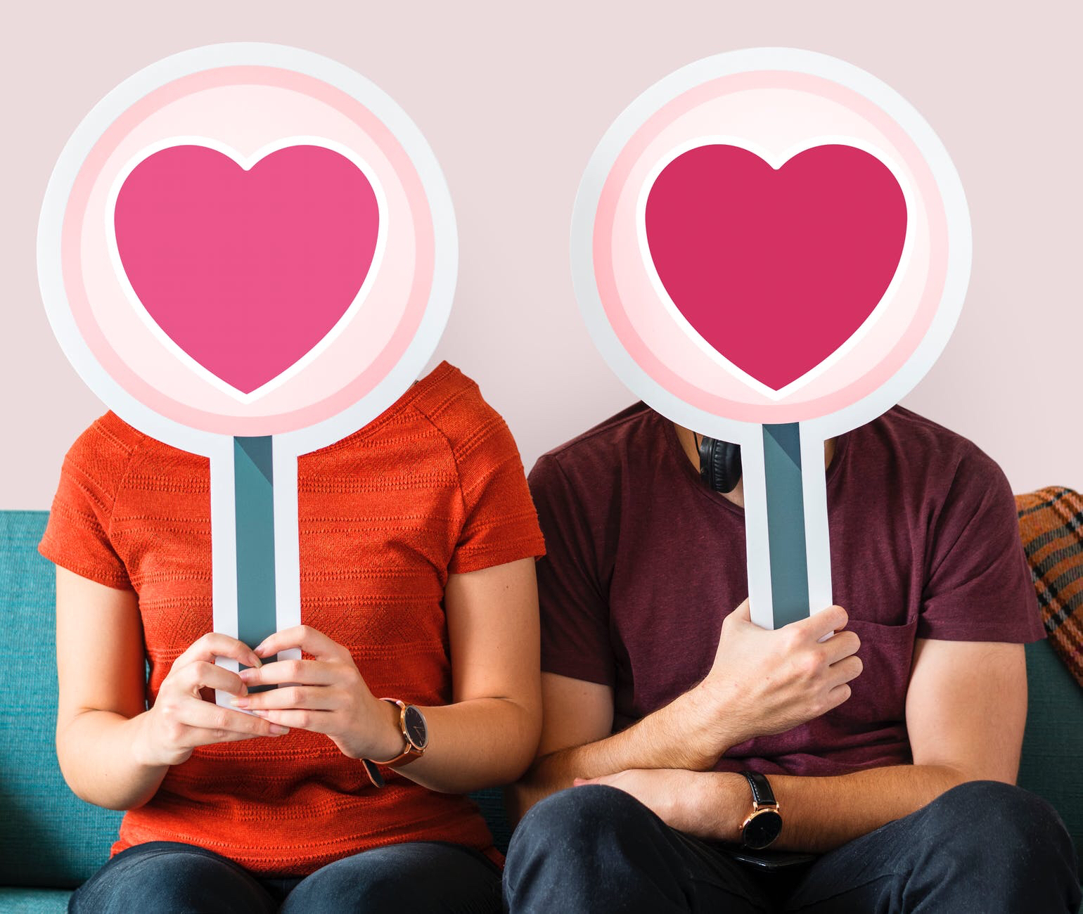 Man and woman holding heart signs over their faces
