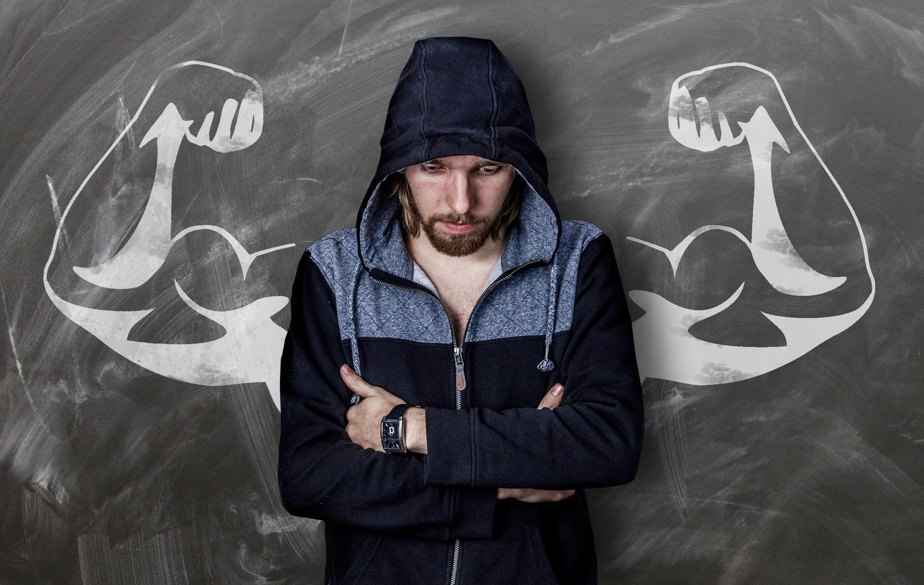 Disappointed man in hoody stands with muscular chalk arms either side