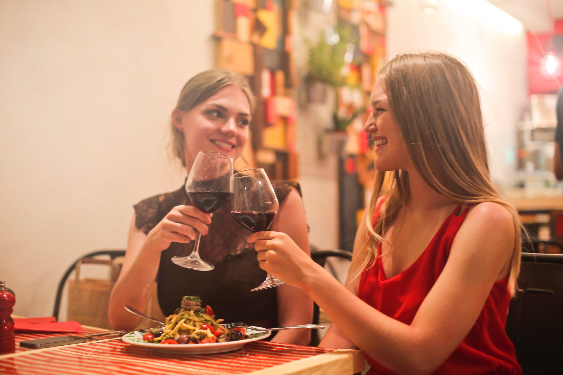 Two women have red wine at dinner