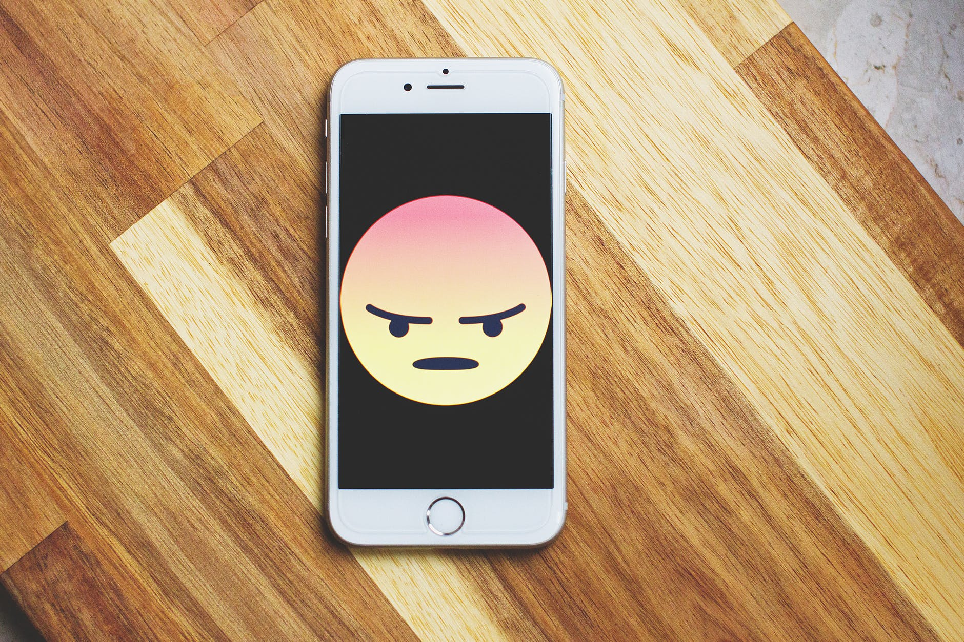 phone with angry face emoji
