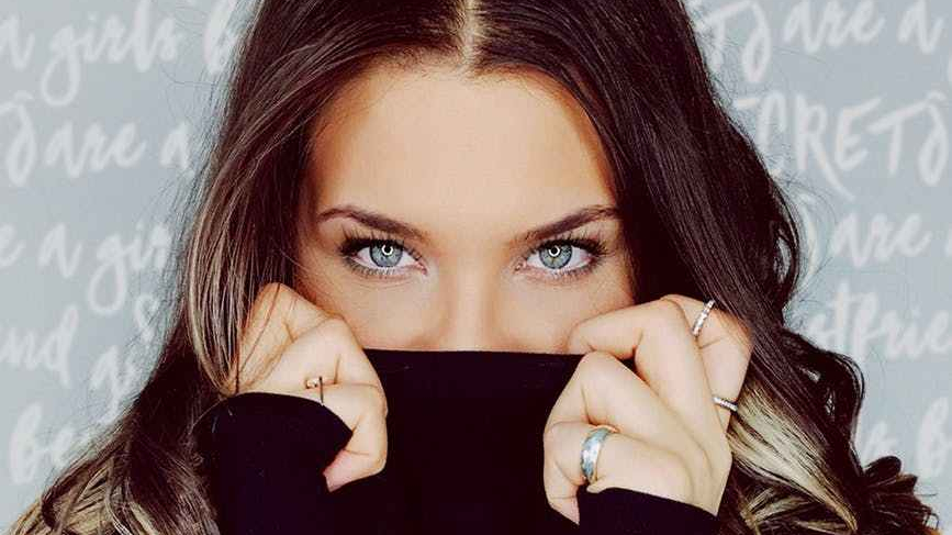 Green eyed woman in black jumper with long hair