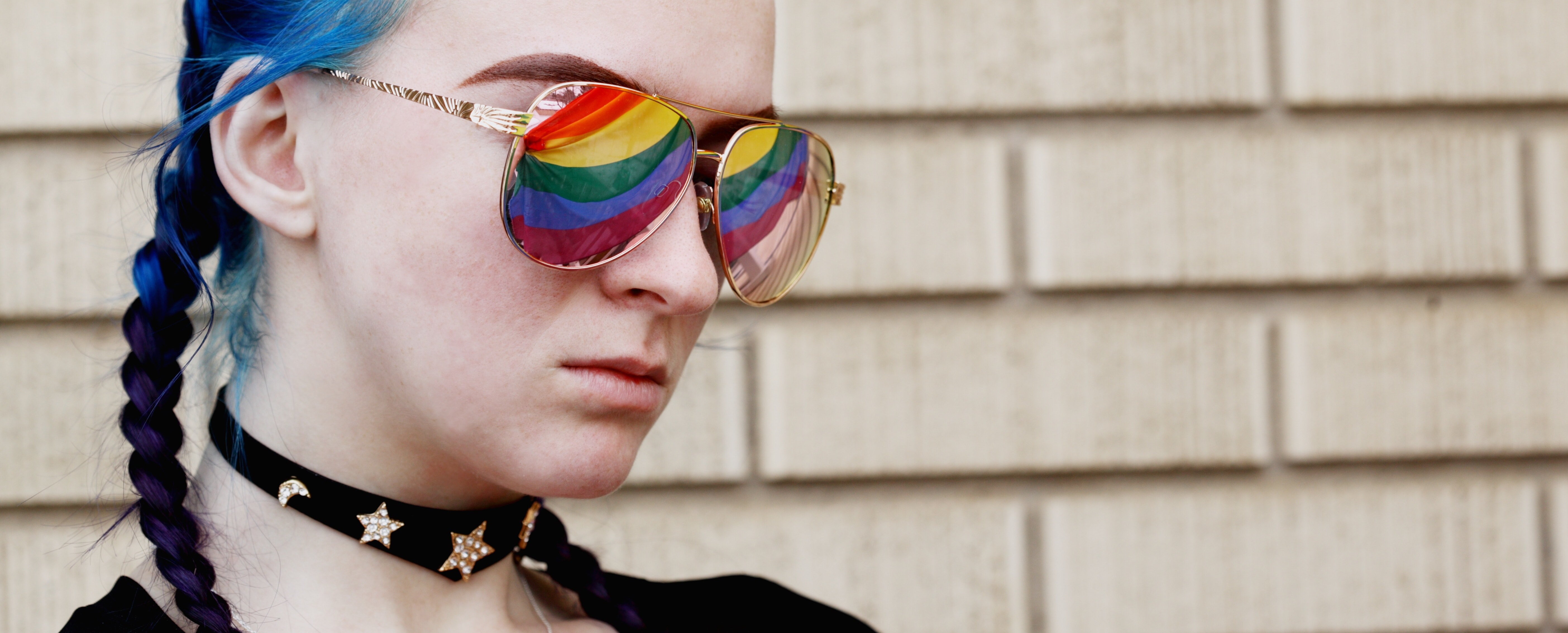 blue hair in braids woman with sunglasses on showing rainbow flag reflection