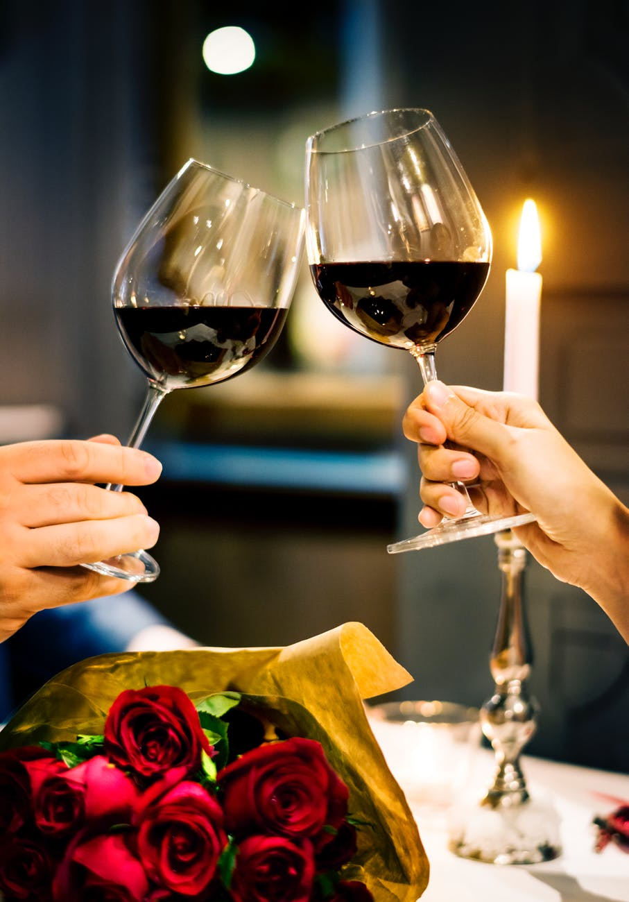Two glasses of red wine over red roses and a candle
