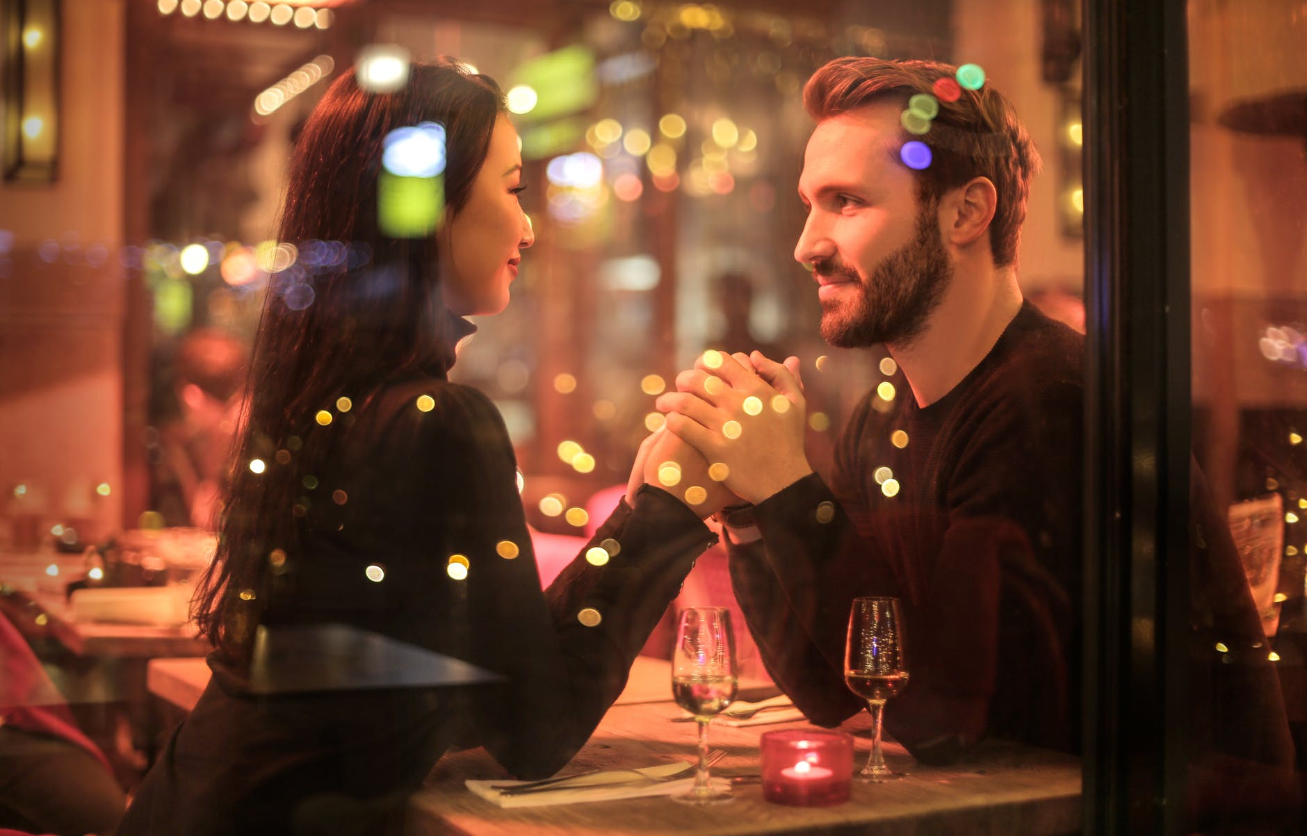 man and woman on a date at dinner with coloured lights around