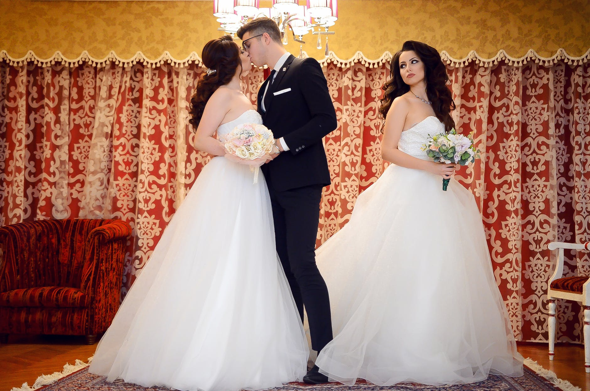 Two women in bridal gowns, one kissing the groom, the other lookig back at them