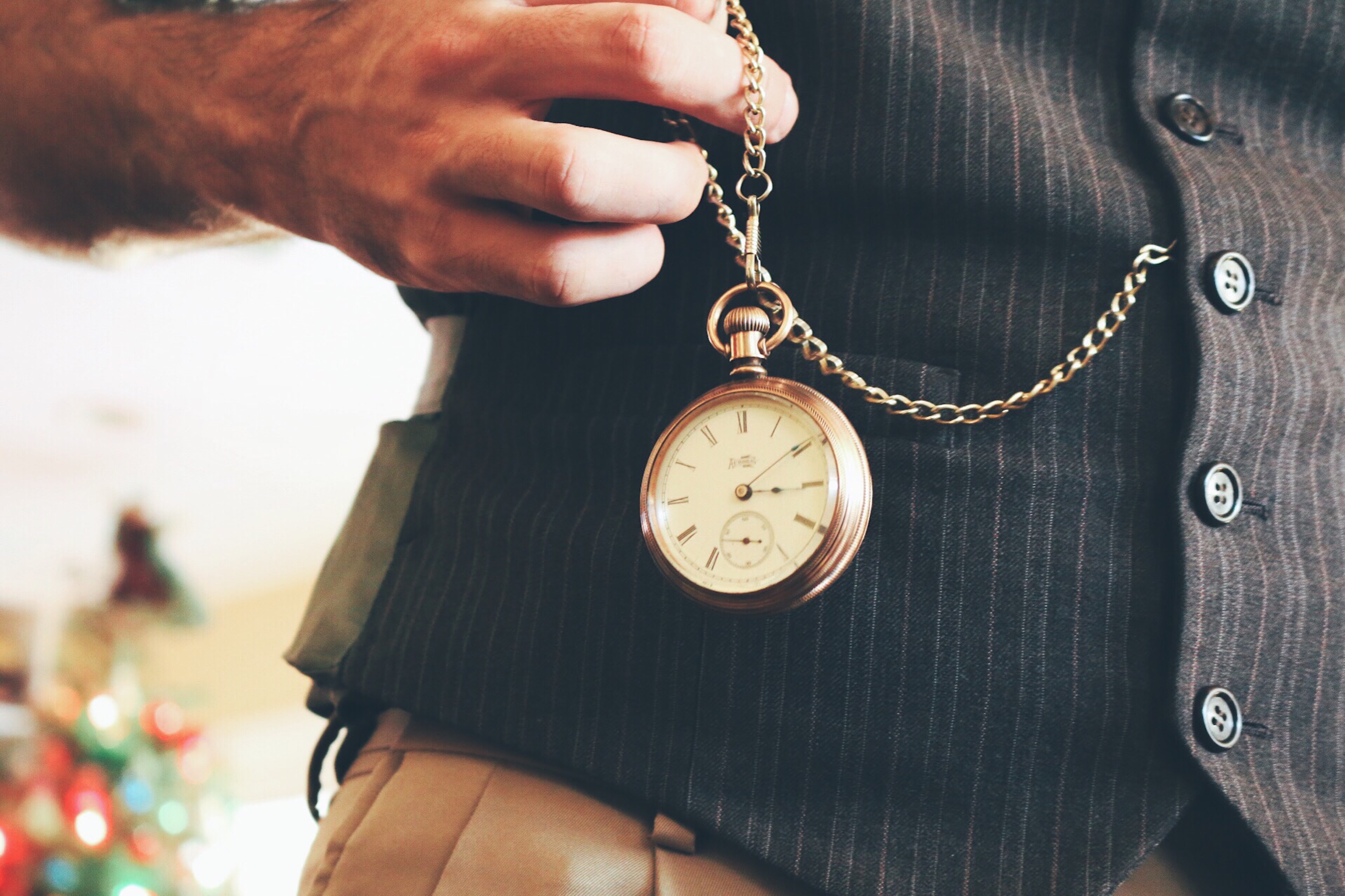 Pocket watch held next to a waistcoat
