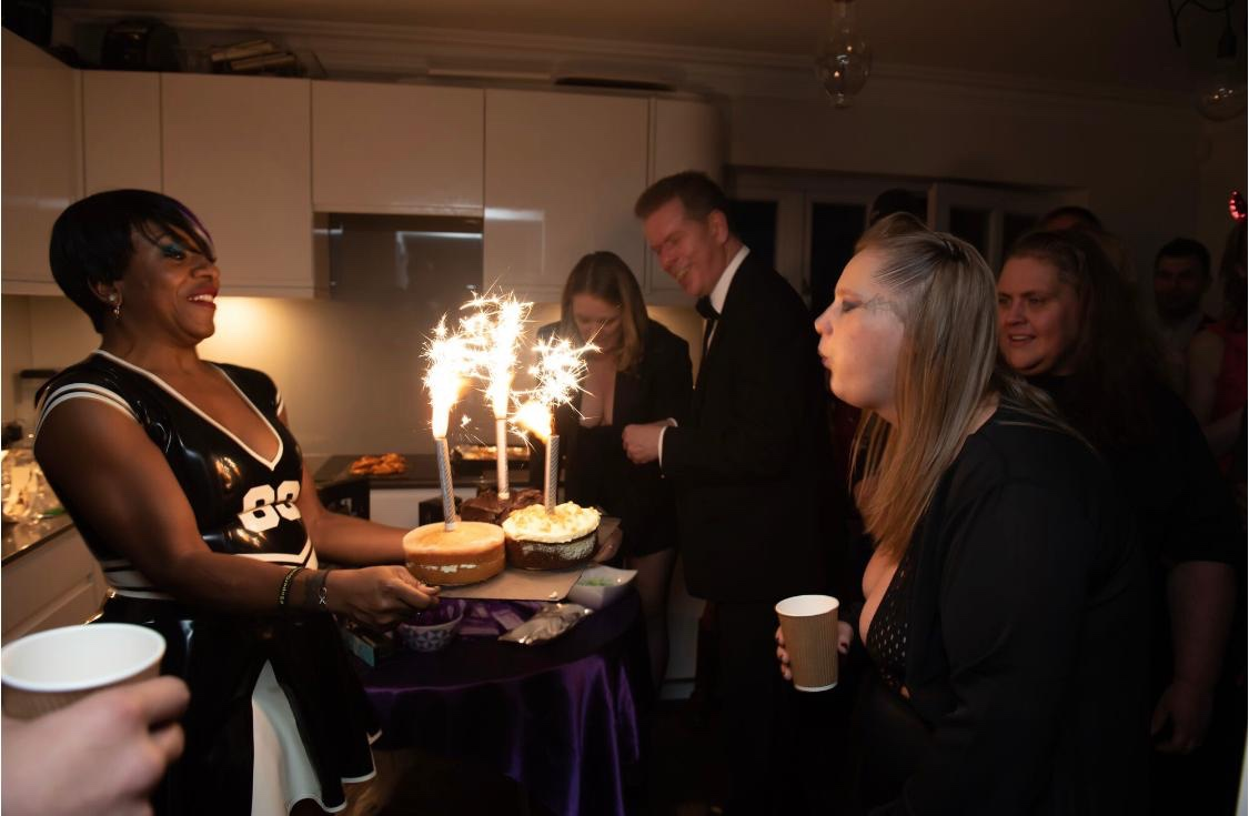 A birthday cake with sparkler fountains is presented to Secrets, a blonde woman, with others in the background
