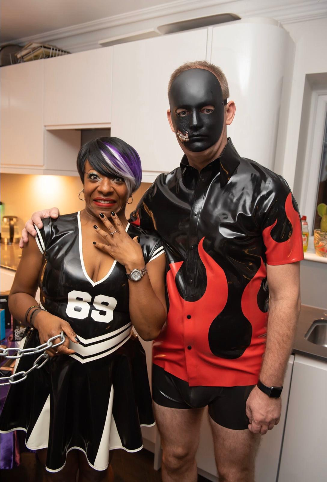 A woman in a rubber dress and a man in a mask and rubber attire stand together