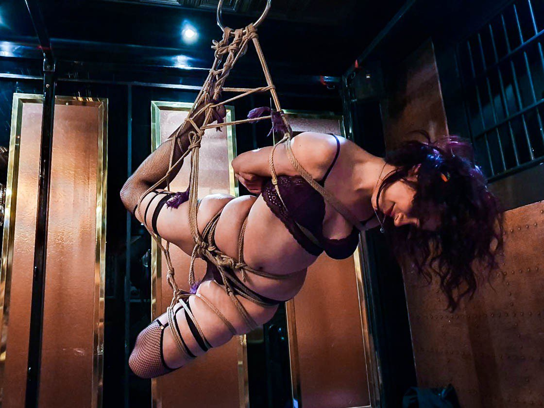 brunette woman and rope bunny hangs happily from a shibari rope ring suspension