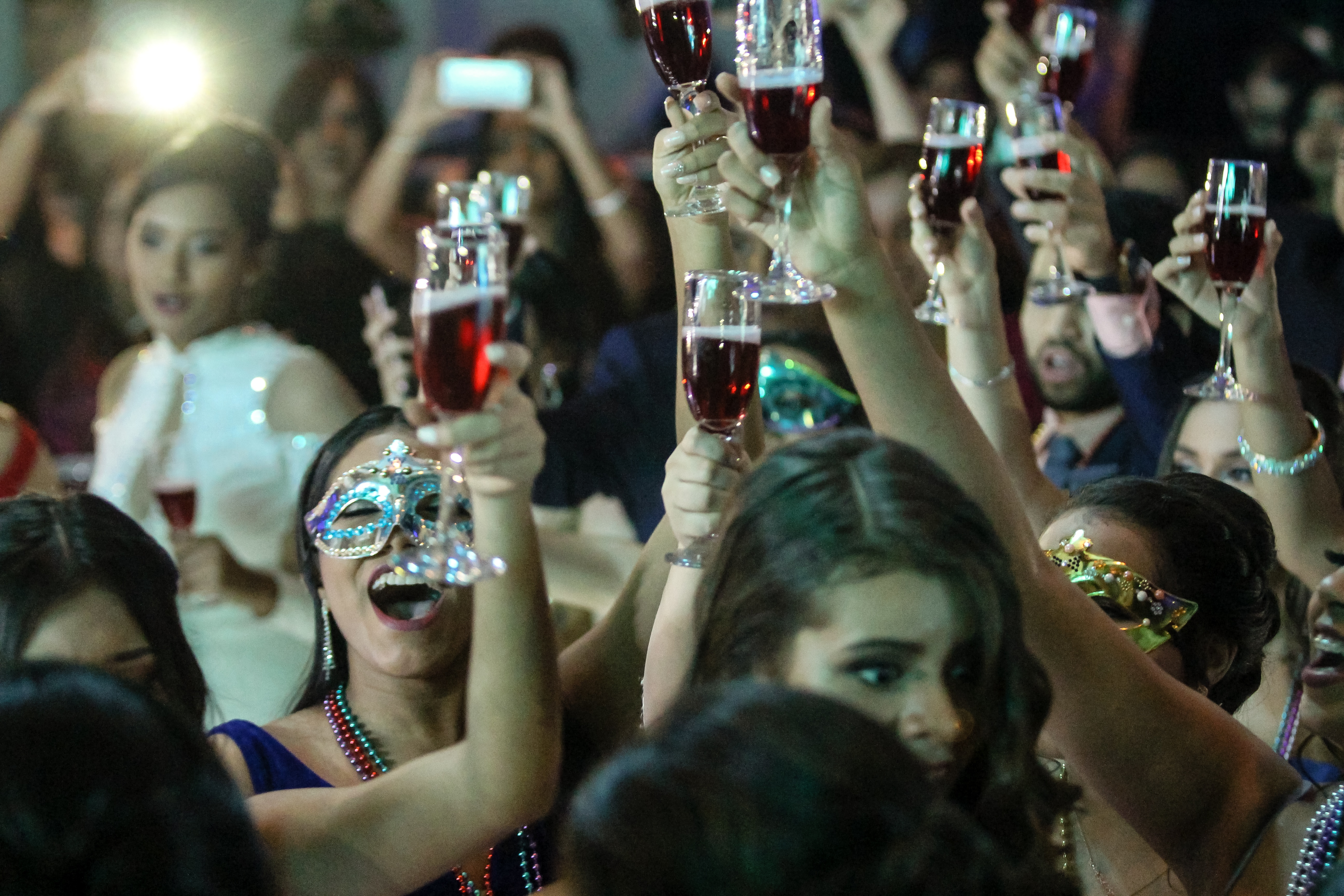 A group of women in party masks holding up glasses of pink champagne