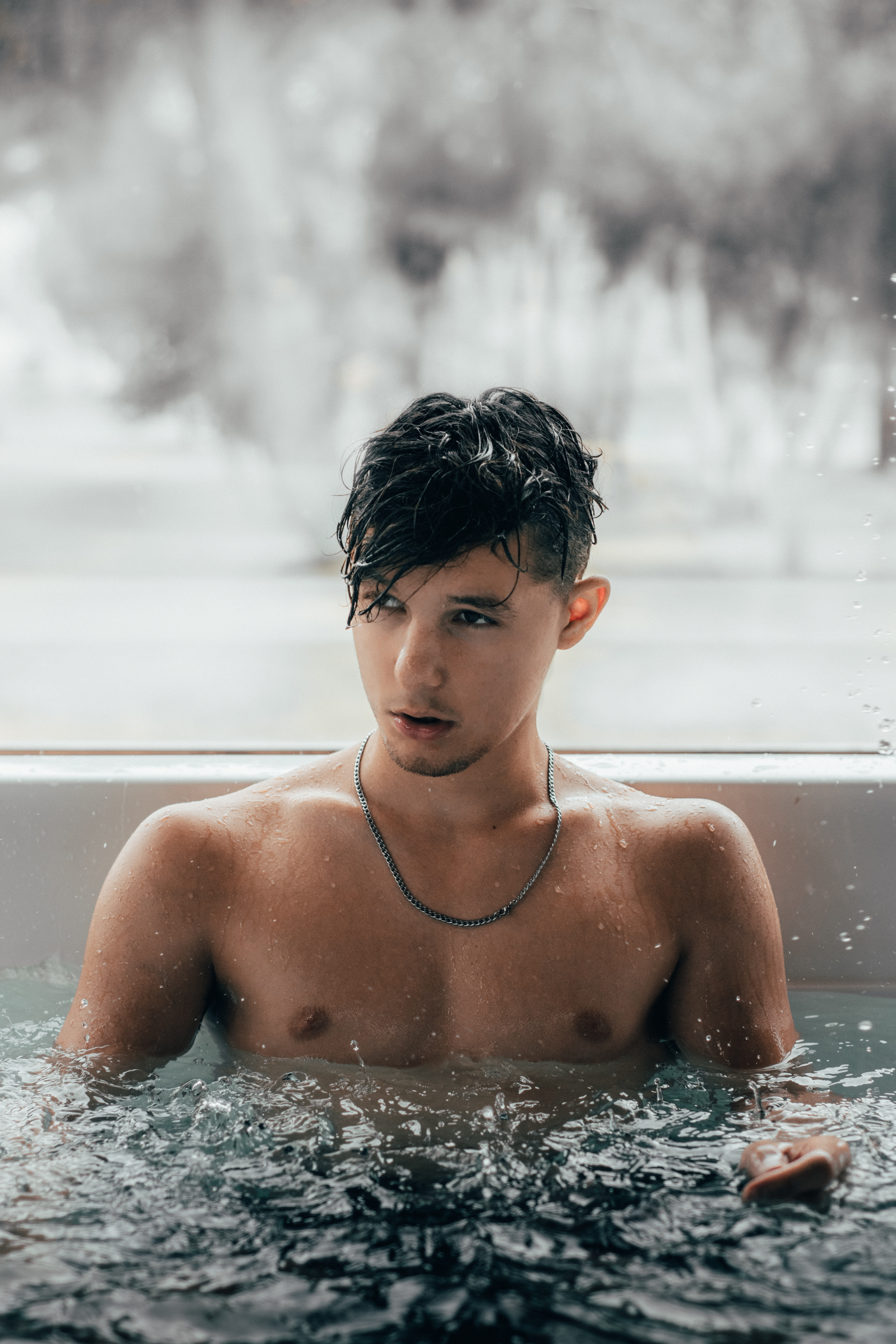 Young man with brown hair enjoying a hot tub in a spa, which is not Rios naturist spa, Kentish Town, London