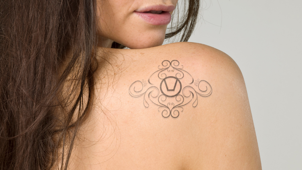 Swinger symbol tattoo on the shoulder of a brunette woman