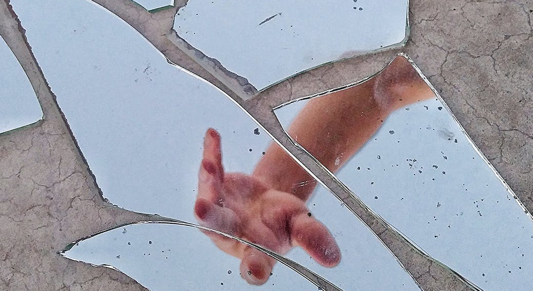 broken mirror reflecting the hand of a white man