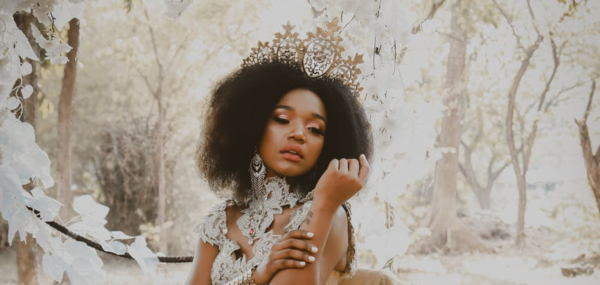 black woman as a queen in a golden woodland landscape