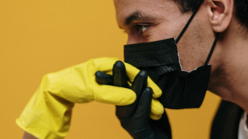 Man in facemask kisses the hand of a woman in rubber gloves