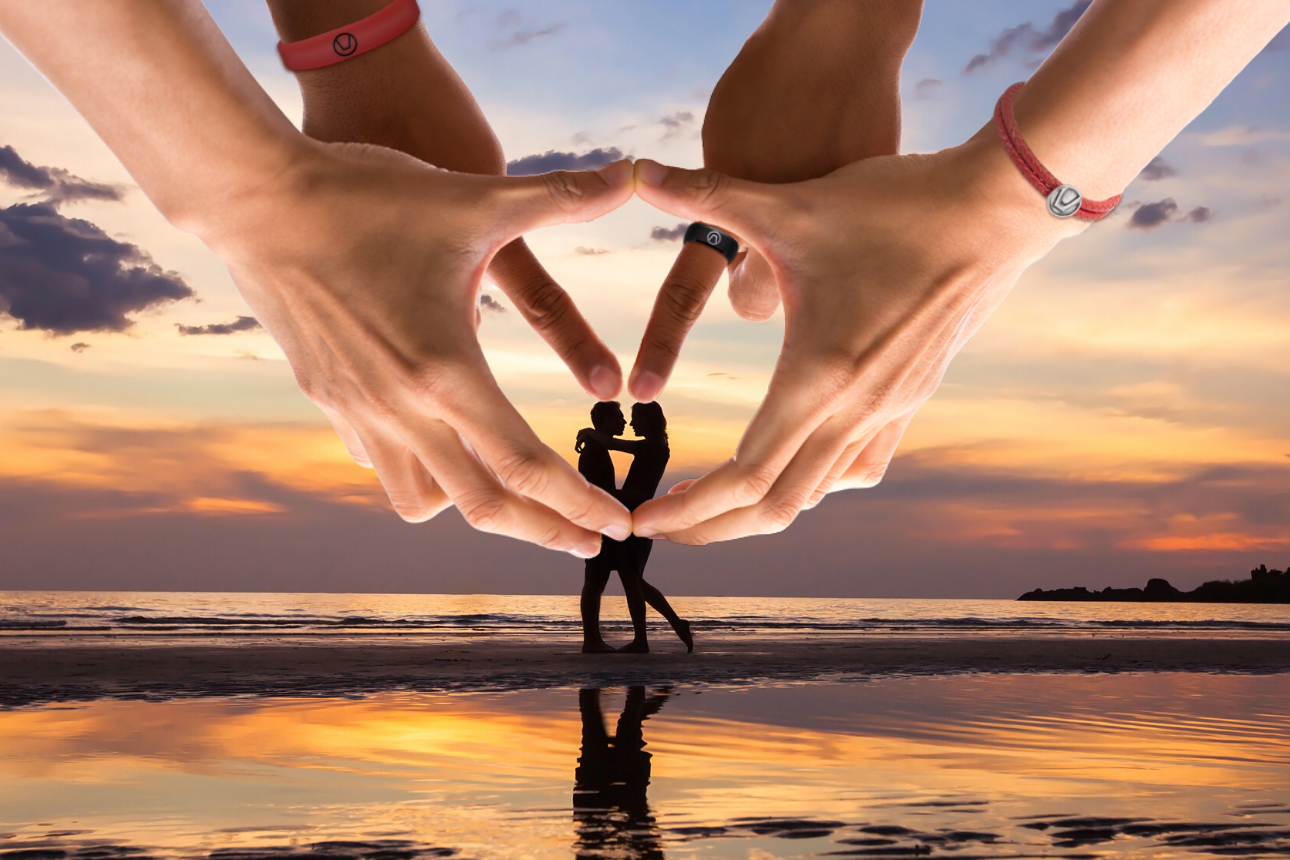 Hands positioned to make the swinger symbol in front of people on a beach