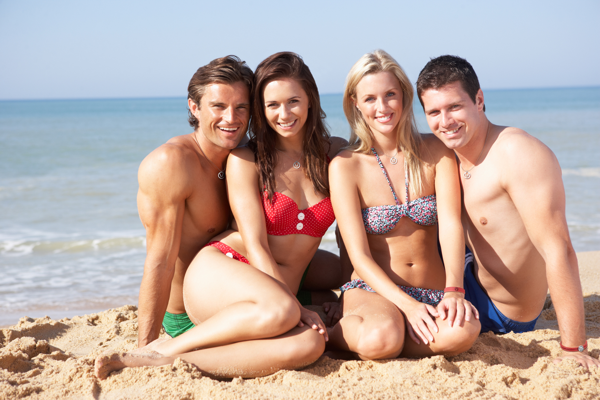 Four silver swinger symbol necklaces on two women and two men at the beach in swimsuits