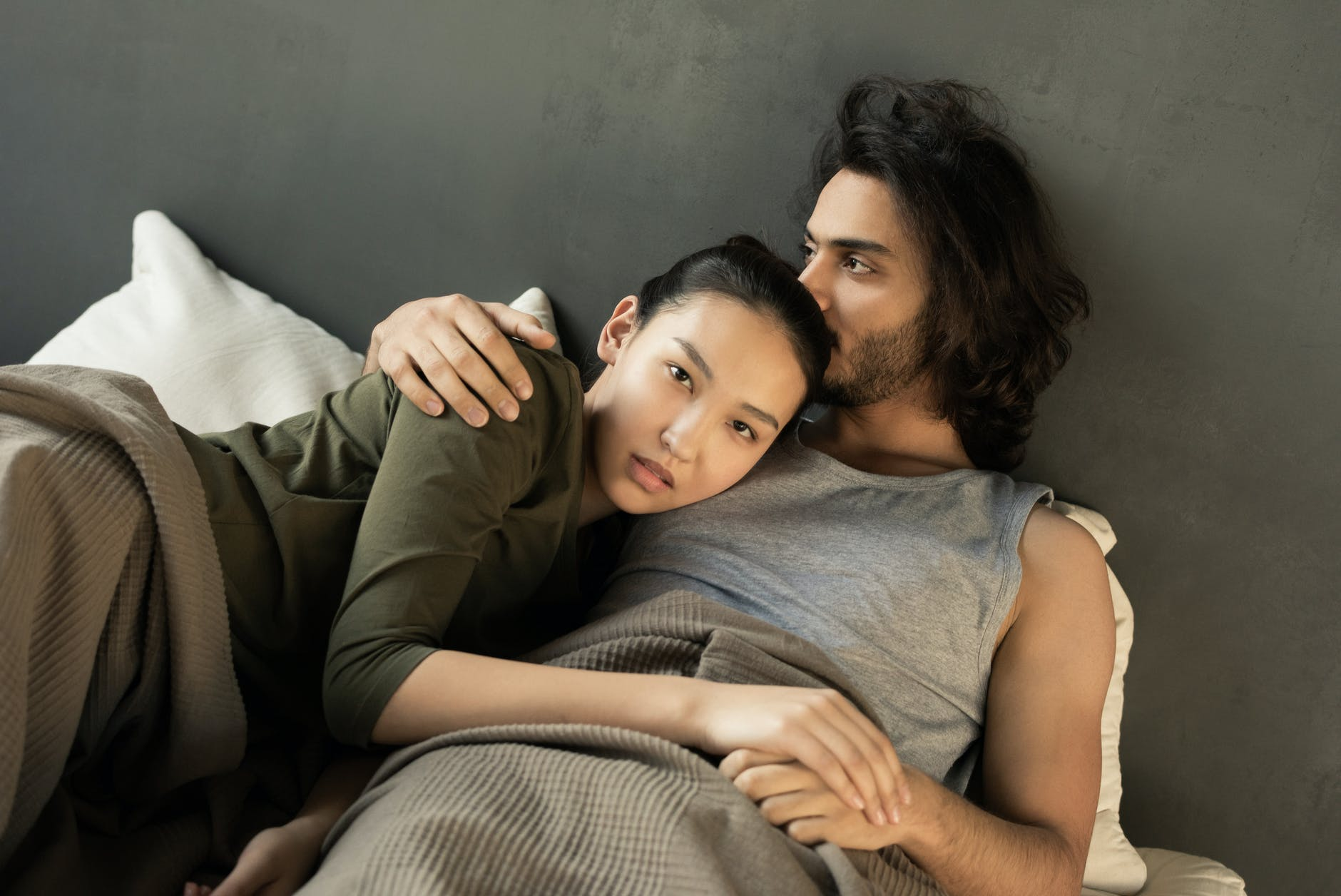 Bearded Asian man and an Asian woman cuddle in bed with green sheets