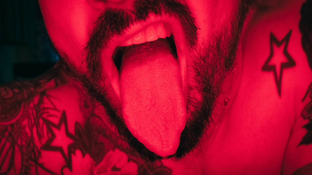 A male tongue and teeth exposed in red light with beard and tattoos- our online male sexworker poses