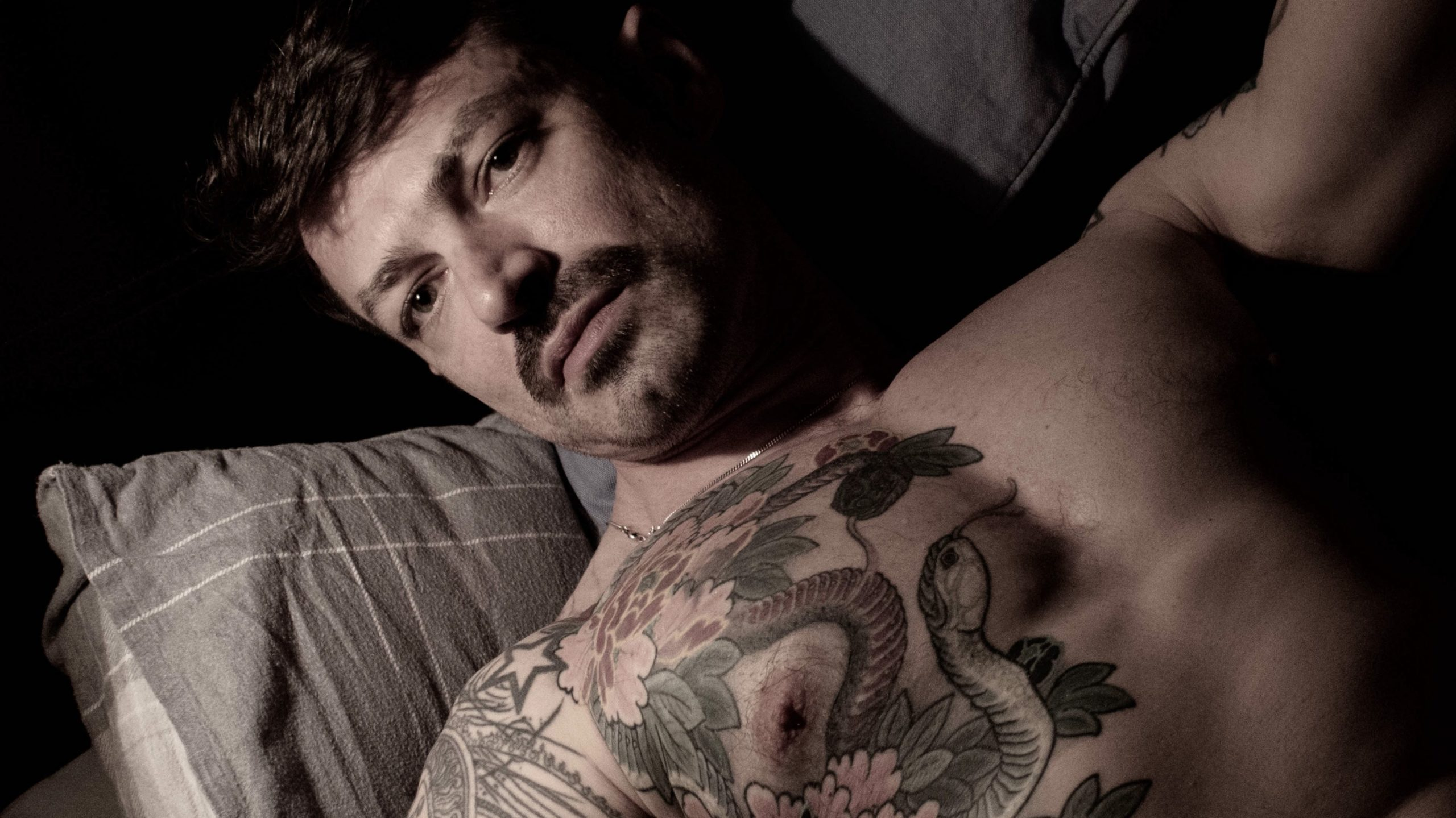 online male sexworker poses in bed showing bearded face and tattoos