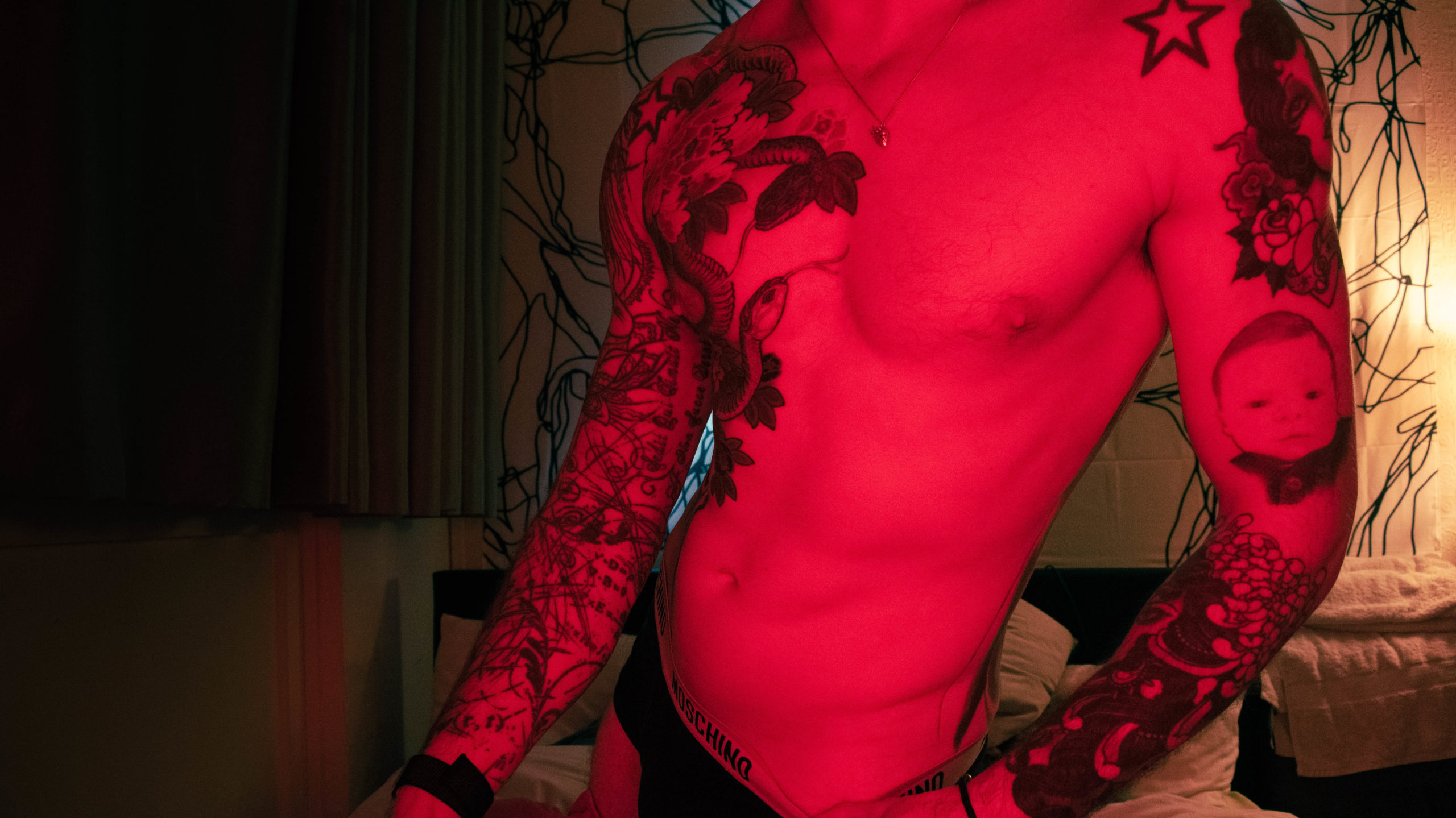 tattooed male torso and underwear in red light