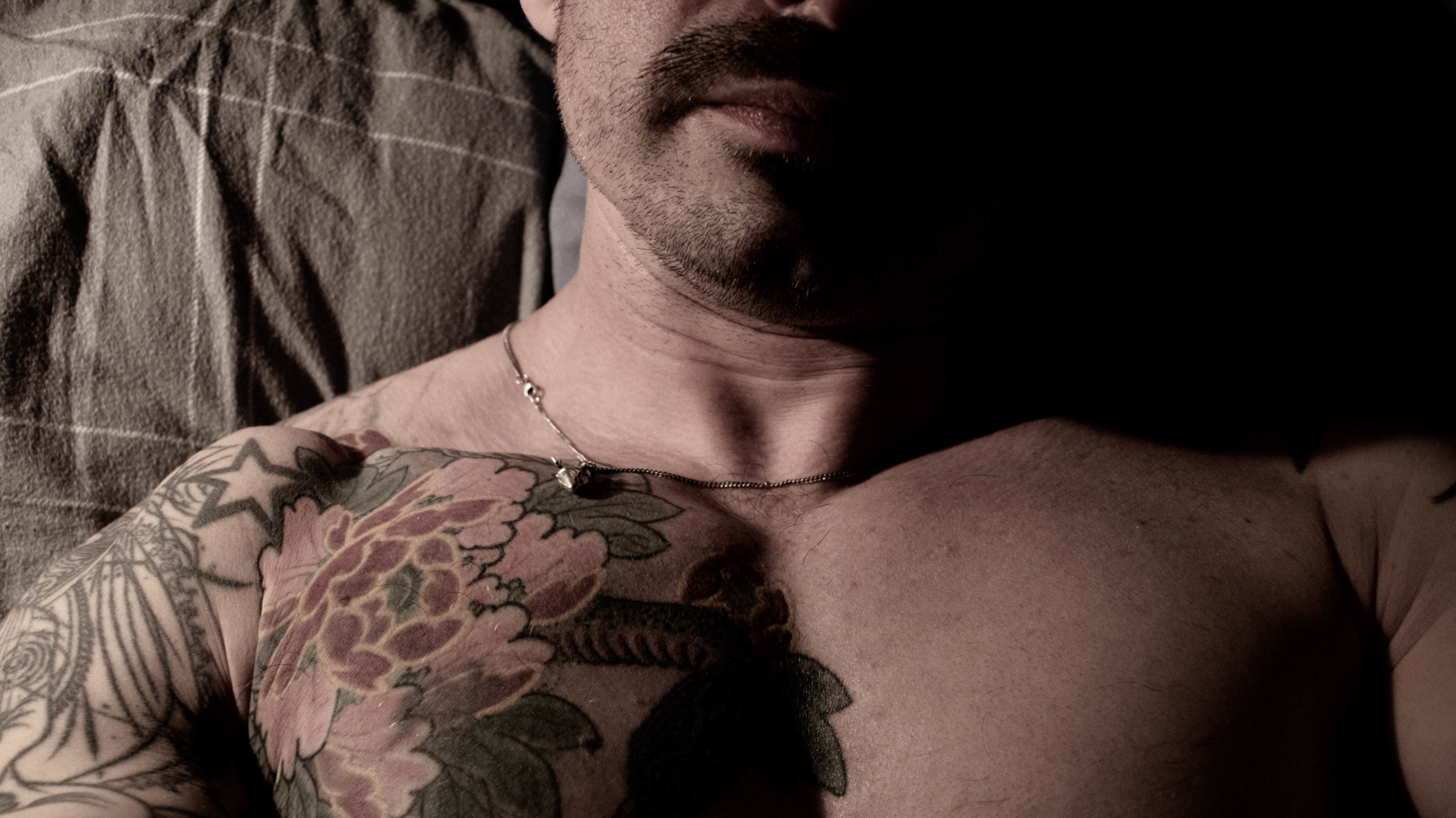 Tattooed torso and lower face of male online sex worker wearing necklace