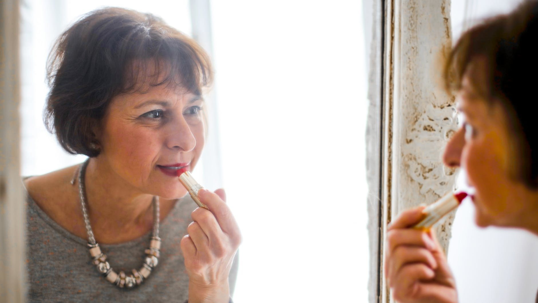 photo of older woman applying lipstick in front of the mirror.  Dating, preparation and investment