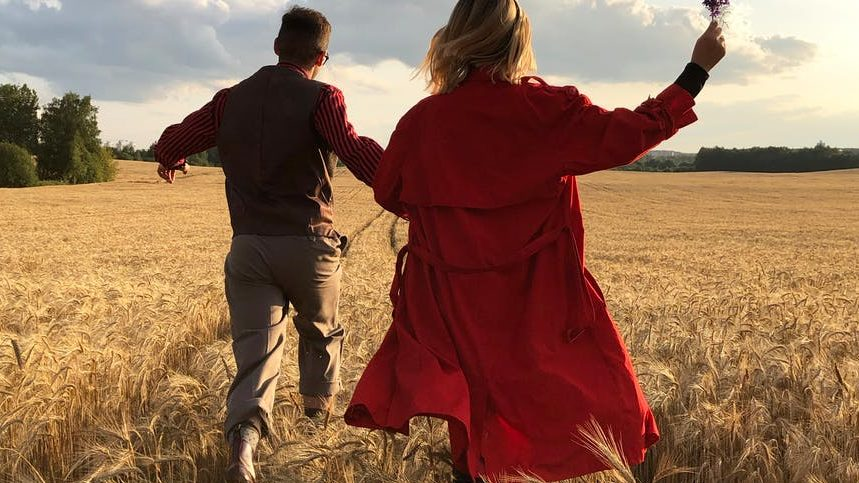 man and woman holding hands and running on a field.  Perhaps she is chasing him to date?
